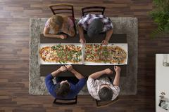 Four friends getting ready to eat two large pizzas, overhead view Stock Photos