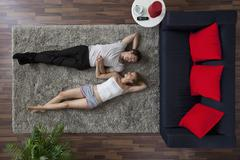 A couple lying on a living room rug, holding hands and gazing at each other, Stock Photos