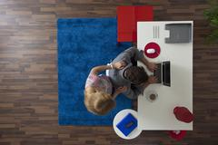 A woman standing behind her man while he works in his home office, overhead view Stock Photos