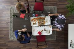 Three friends relaxing around a table after eating pizza, overhead view Stock Photos