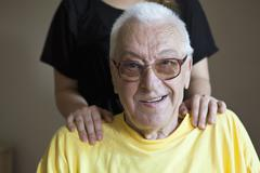 A senior man in a nursing home, hands on his shoulders, focus on him Stock Photos