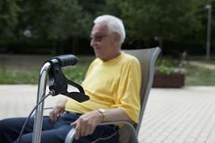 A senior man sitting in a chair, the handle of his walker in the foreground, Stock Photos