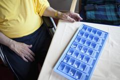 A senior man sitting next to a weekly pill organizer, focus on object Stock Photos