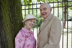 Senior couple in park smile at camera Stock Photos
