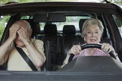 Woman has trouble driving while man in passenger seat despairs Stock Photos
