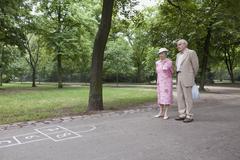 Senior couple contemplate hopscotch in the park Stock Photos