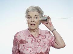 Senior woman comically strains to listen as she holds a tin can phone to her - stock photo