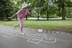Senior woman plays hopscotch trying to keep her balance Stock Photos