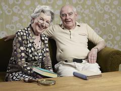 Senior man and woman with books on the couch Stock Photos