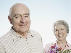 Senior man looks pleased that she likes the flowers Stock Photos