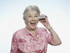 Senior woman comically listens to tin can phone - stock photo