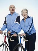 Senior man and woman holding racing bicycles - stock photo