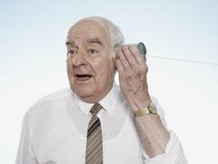 Senior man listening on tin can phone Stock Photos