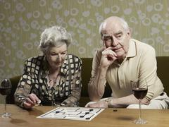 Senior couple play muehle and man looks impatient Stock Photos