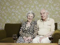 Husband and wife relaxed on sofa, with two glasses of red wine on table in front Stock Photos
