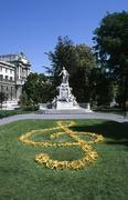 Austria, Vienna, Mozart statue in Burggarten Park and a floral treble clef in Stock Photos