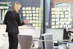 Businesswoman sticking many reminder notes to her office window Stock Photos