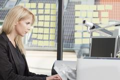 Businesswoman concentrating as she types on office computer Stock Photos
