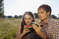 Couple in field eating a melon Stock Photos