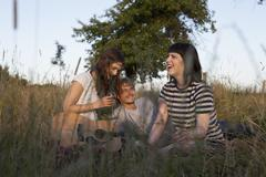 Three friends enjoying sitting in secluded field with wine and guitar - stock photo