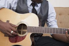 Stock Photo of A young man playing an acoustic guitar, focus on midsection