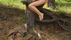 Pretty girl in swimsuit sitting on the branch on the sea shore, enjoys vacations Stock Footage