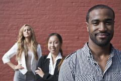 Portrait of a man in front of two female colleagues Stock Photos