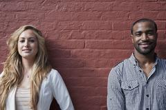 Portrait of a young woman and a man leaning against a wall - stock photo