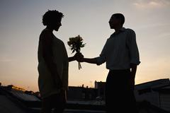 Stock Photo of A man giving flowers to a woman on a rooftop terrace at sunset