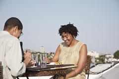 Over the shoulder view of a couple eating a meal on a rooftop terrace - stock photo