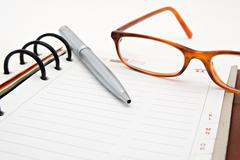 Opened notebook with pen and glasses Stock Photos