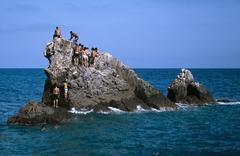 A group of men on a stack rock in the sea Stock Photos