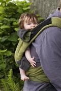 A father carrying his baby daughter in baby carrier, focus on baby Stock Photos