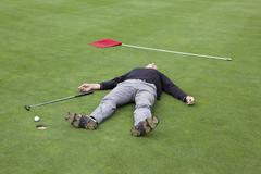 A distraught golfer lying on putting green with ball at the edge of hole - stock photo