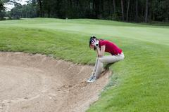 A female golfer sitting at the edge of sand trap, head in hands Stock Photos