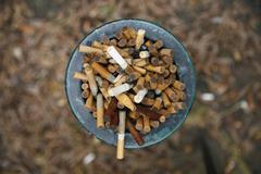 Ashtray full of cigarettes outside Stock Photos