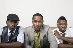 Three men sitting side by side looking surprised Stock Photos