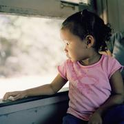 A child sitting on her mother's lap riding on a train - stock photo