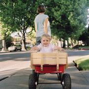 A mother pulling her young son in a wagon, focus on boy Stock Photos