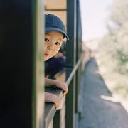 An excited boy leaning out of a train window Stock Photos