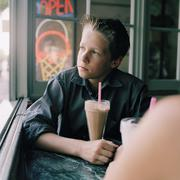 A serious teenboy with a milkshake looking out a window Stock Photos