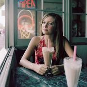 A teengirl sitting at a table with a milkshake - stock photo
