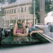 A young teencouple sharing a milkshake at a diner, viewed through window Stock Photos