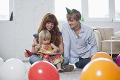 Two young parents with their daughter, celebrating her birthday - stock photo