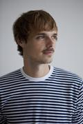 A young man in a striped t-shirt looking away Stock Photos