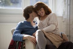 A young man kissing his girlfriend who's sitting on his lap - stock photo