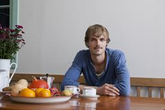 A young man having breakfast, looking at camera Stock Photos