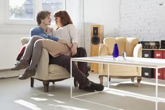 A young woman sitting comfortably in her boyfriend's lap - stock photo