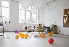 Multi colored balloons on the floor of a modern living room Stock Photos