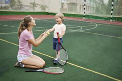 A mother and son having fun on tennis court - stock photo